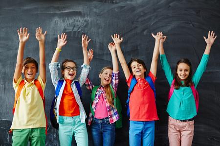 Foto de Ecstatic kids raising hands while standing by blackboard - Imagen libre de derechos