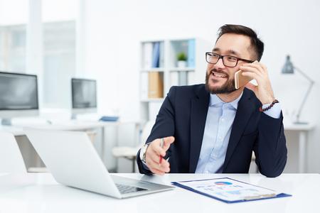 Foto de Asian businessman sitting at his workplace and talking on the phone - Imagen libre de derechos