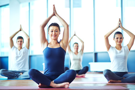 Foto de Young woman practicing yoga in yoga class in fitness center - Imagen libre de derechos