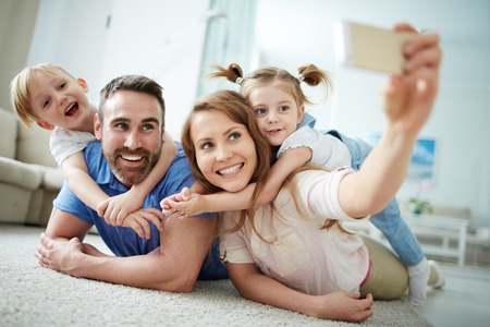 Photo pour Happy young family taking selfie on the floor at home - image libre de droit
