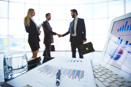 Business documents in clipboard, pen, glass of water and touchpad with business partners on background