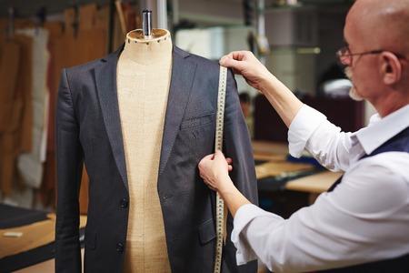 Foto de Tailor with measuring tape taking measures of jacket on mannequin - Imagen libre de derechos