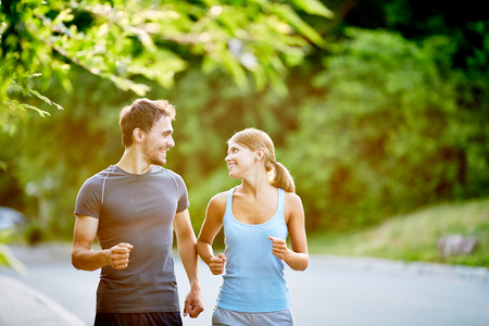 Photo pour Young couple running together in summer day - image libre de droit