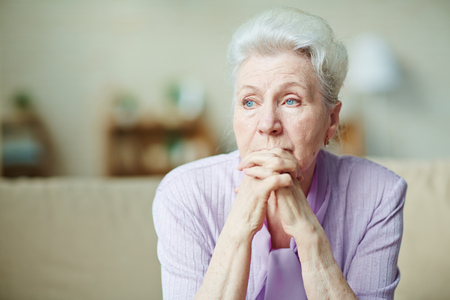 Photo pour Elderly woman keeping hands by her lips - image libre de droit