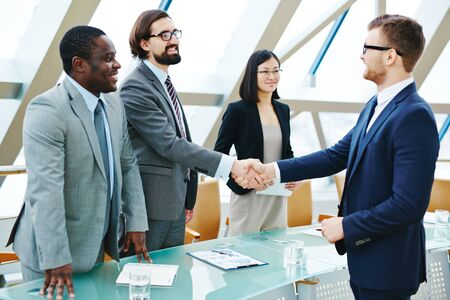 Young businessmen handshaking at meeting after signing contract