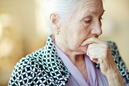 Photo for Pensive senior woman with her hand by mouth - Royalty Free Image