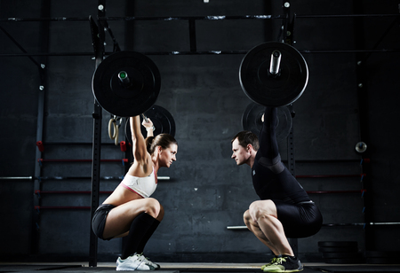 Foto de Active young man and woman lifting heavy barbells opposite one another - Imagen libre de derechos