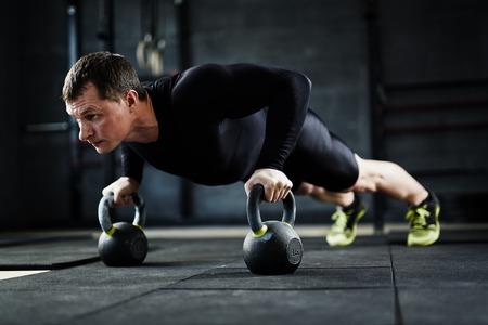 Foto de Active young man doing push-ups in gym - Imagen libre de derechos