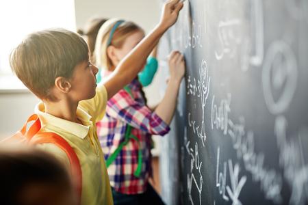 Foto de Clever schoolchildren doing sums on blackboard - Imagen libre de derechos