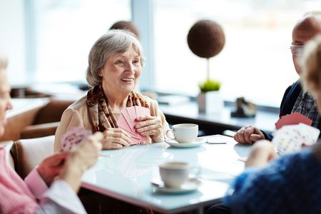 Photo pour Group of seniors meeting every week in cafe to play cards - image libre de droit