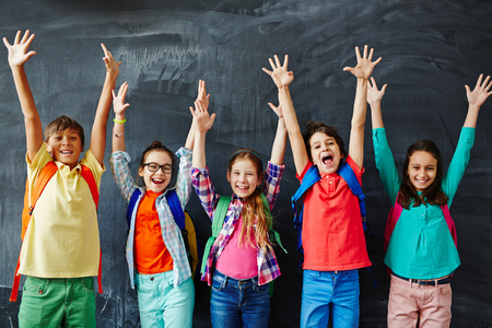 Foto de Excited schoolchildren standing with hands up - Imagen libre de derechos