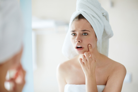 Photo pour Anxious girl looking at pimple on her cheek in mirror - image libre de droit
