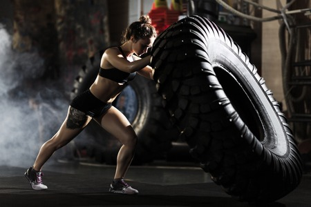 Photo for Strong fit woman flipping tire in gym - Royalty Free Image