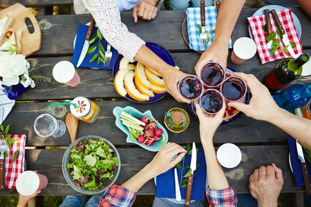 Foto de Hands with red wine toasting over served table with food - Imagen libre de derechos