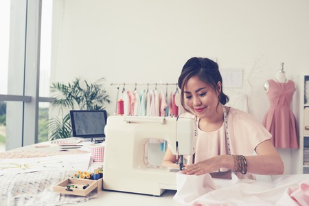 Photo for Smiling fashion designer using sewing machine and sitting behind her desk - Royalty Free Image
