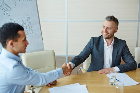 Happy partners handshaking after signing contract
