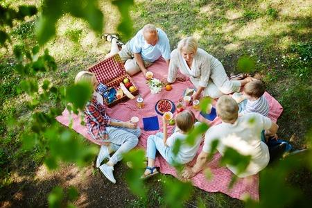 Foto de Three generations having lunch on the ground - Imagen libre de derechos