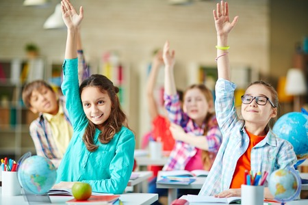 Photo pour Intelligent group of school children raising their hands in to answer a question - image libre de droit