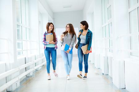 Foto de Group of female students walking along the corridor at college - Imagen libre de derechos
