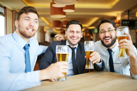 Three formally dressed businessmen in ties with beaming smiles looking at camera celebrating success with beer in bar.