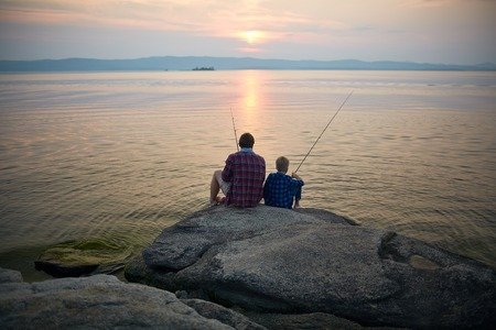 Photo for Two fishermen sitting on stone by lake in the evening - Royalty Free Image