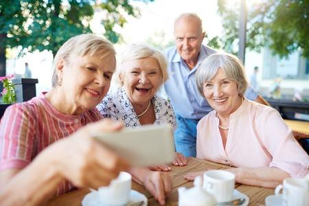 Foto de Happy seniors making selfie during hang-out in outdoor cafe - Imagen libre de derechos