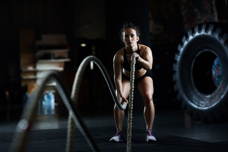 Foto de Sporty woman practicing exercise with battle rope - Imagen libre de derechos