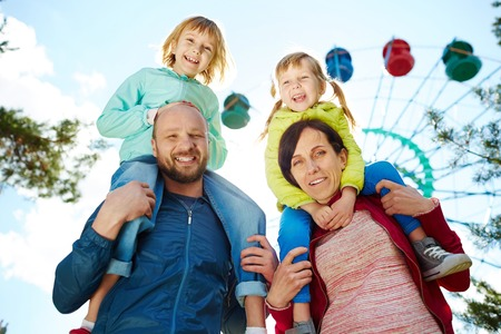 Photo for Low angle view of smiling family in amusement park, mother and father carrying their two adorable blond girls on shoulders and looking at camera during warm autumn weekend, ferris wheel in background - Royalty Free Image
