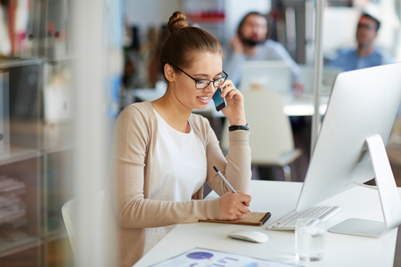 Foto de Young professional businesswoman working in public relations talking on phone with partners making notes in small notebook, sitting at computer desk in modern office space - Imagen libre de derechos