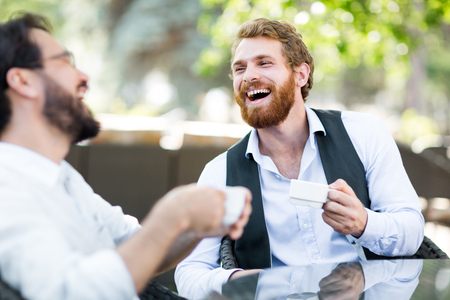 Foto de Friendly young men with coffee talking in outdoor cafe - Imagen libre de derechos