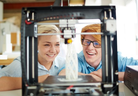 Photo pour Two happy engineers looking at architectural model in 3d printer - image libre de droit