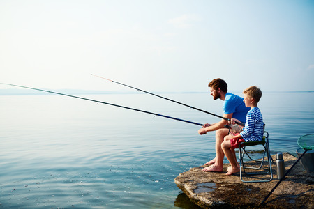 Photo for Young man and little boy fishing together - Royalty Free Image