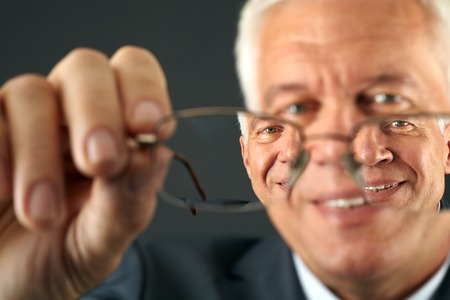 Photo pour Close-up of eyeglasses and man looking through them - image libre de droit