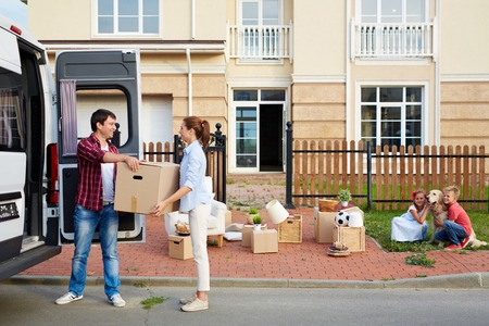 Photo pour Young man giving his wife box while unloading things from van - image libre de droit