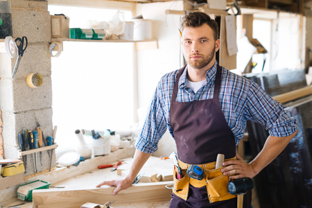 Photo for Contemporary carpenter with tool-belt looking at camera in workshop - Royalty Free Image
