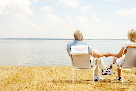 Foto de Rear view of senior couple resting in chaise lounges on lakeside and holding hands - Imagen libre de derechos