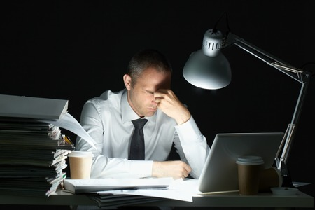 Photo pour Businessman sitting at office desk full with papers being overloaded with work - image libre de droit