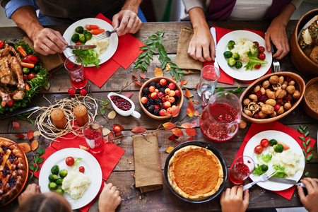 Photo pour Above view of thanksgiving dinner and family eating at table - image libre de droit
