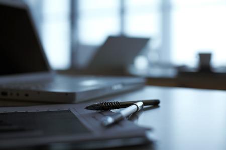 Foto de A notebook and pens lying on table with laptop on background - Imagen libre de derechos