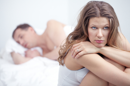 Photo for Dissatisfied woman sitting by bed where her husband is sleeping - Royalty Free Image