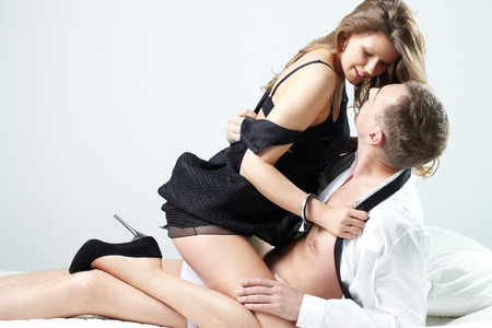 Foto de A young woman tempting a man on bed - Imagen libre de derechos