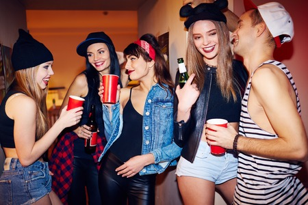 Photo pour Cool students hanging out drinking beer and talking in corridor of big private house at swag party - image libre de droit