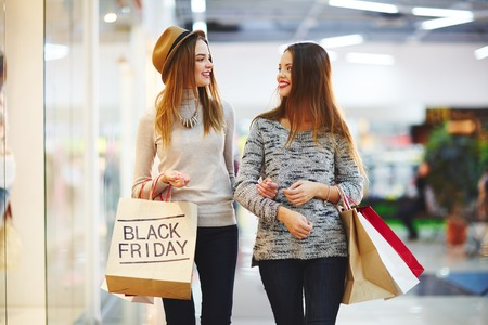 Photo for Shoppers carrying paperbags and talking at Black Friday sale - Royalty Free Image