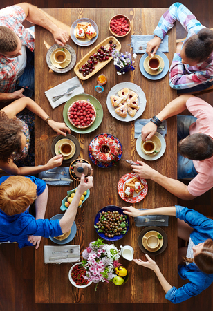 Photo for Group of young people sitting by festive table and eating Thanksgiving food - Royalty Free Image