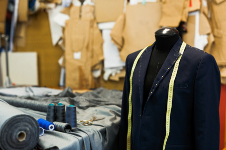 Photo for Unfinished jacket on dummy and sewing accessories in tailoring shop - Royalty Free Image
