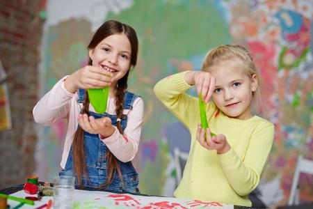 Foto de Two friendly girls with slime having fun in kindergarten - Imagen libre de derechos