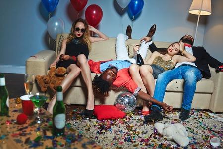 Foto de Tipsy friends in messy living room - Imagen libre de derechos
