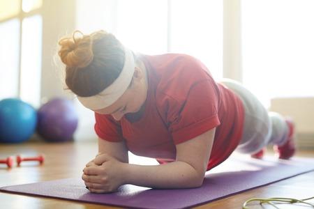 Photo pour Obese Woman Holding Plank Exercise in Fitness Studio - image libre de droit