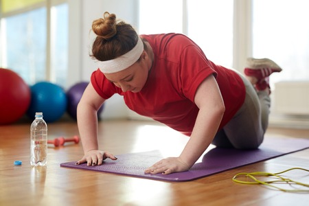Foto de Obese Woman Doing Push Up Exercises to lose Weight - Imagen libre de derechos