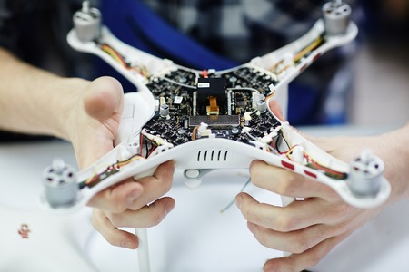 Photo pour Closeup shot of male hands holding opened drone showing main circuit board and micro controller unit to camera against white table in workshop - image libre de droit
